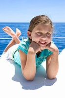 Girl 8-10 lying on front on deck of sailing boat out at sea, smiling, portrait