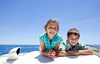 Boy and girl 8-10 lying on front on deck of sailing boat out at sea, side by side, smiling, front view, portrait