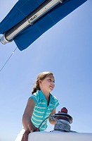 Girl 8-10 winding rope pulley of boat rigging on deck of sailing boat out at sea, smiling, low angle view