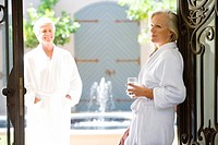 Mature couple wearing white bath robes, man outside smiling at woman standing in doorway