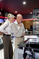 Mature couple shopping in computer store, looking at laptop