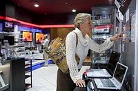 Mature woman shopping in computer store, standing by laptops, side view