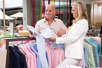 Mature couple in clothing store, holding shirt, smiling