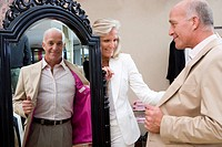 Mature couple in clothing store, man trying on jacket in front of mirror, smiling