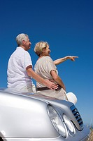 Senior couple leaning against parked car bonnet on clifftop overlooking ocean, woman pointing, rear view