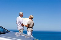 Senior couple standing beside parked car on clifftop overlooking Atlantic Ocean, consulting map, rear view
