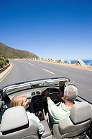 South Africa, Western Cape, senior couple driving in convertible car along coastal road, smiling, rear view, elevated view