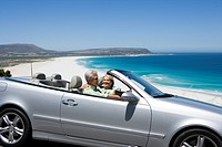 South Africa, Western Cape, senior couple driving in convertible car along coastal road, smiling, side view