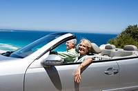 South Africa, Western Cape, senior couple driving in convertible car along coastal road, smiling, side view, portrait