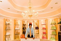 Male shop assistant standing in front of designer handbags on shelf display in glamorous boutique, smiling, front view, portrait