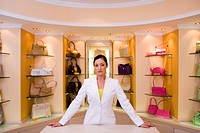 Female shop assistant standing in front of designer handbags on shelf display in glamorous boutique, front view, portrait