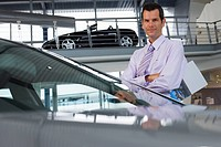 Car salesman standing beside new saloon cars in showroom, holding brochure, smiling, portrait
