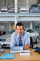 Car salesman sitting at desk in car showroom, smiling, front view, portrait (thumbnail)