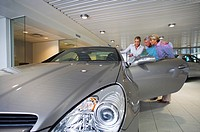 Car saleswoman showing senior couple new silver convertible car in large showroom, smiling