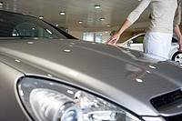 Woman stroking bonnet of new silver car in showroom, side view, mid-section