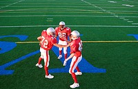 Two American football players congratulating teammate on pitch during competitive game, elevated view