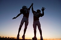 Two American football players celebrating on pitch at sunset, jumping up, doing high-fives backlit