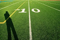 Man casting shadow on American football pitch at 10 yard line