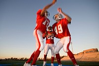Two American football players, in red football strips, celebrating touchdown on pitch at sunset, jumping chest to chest, teammate looking on, low angl...