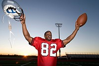 American football player, in red football strip, celebrating victory on pitch at sunset, arms up, holding ball and protective helmet, cheering