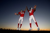 Two American football players celebrating on pitch at sunset, jumping up, doing high-fives, low angle view backlit
