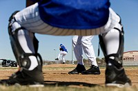 Baseball batter facing pitcher during competitive game, view through catcherÔÇÖs legs, rear view, focus on background