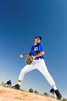 Baseball pitcher, in blue uniform, preparing to throw ball during competitive game surface level, tilt