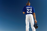 Baseball player standing against clear blue sky, carrying bat on shoulder, rear view, low angle view