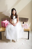 Girl 8-10, dressed in bridesmaid dress, sitting beside wedding gift on bench, smiling, front view, portrait