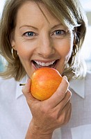 Mature woman eating apple, close-up, front view, portrait