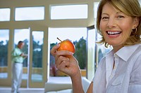 Mature woman eating apple at home, senior man in background, focus on woman, smiling, side view, portrait