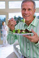 Senior man eating salad on plate at home, mature woman in background, focus on man, smiling, portrait
