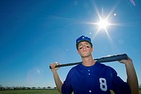 Baseball player, in blue uniform and cap, standing on pitch with bat behind head, front view, portrait lens flare