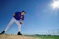 Baseball pitcher, in blue uniform, preparing to throw ball during competitive game (thumbnail)