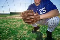 Baseball player, wearing number ÔÇÿ25ÔÇÖ blue uniform and glove, crouching on pitch, close-up, low section