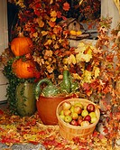Decorated porch with pumpkins, gourds, apples and fall leaves