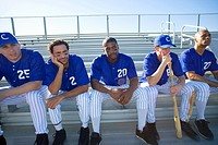 Dejected baseball team sitting on bench in stand during competitive baseball game, looking gloomy, front view backlit