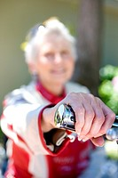 Senior woman sitting on motorbike on driveway, smiling, portrait, focus on handlebar in foreground
