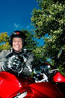 Senior man, wearing crash helmet and gloves, standing beside red motorbike on driveway, smiling, portrait, low angle view
