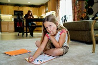 Young girl does her homework, mother in background