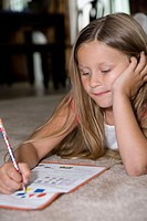 a young girl does her homework. age 5_7yrs