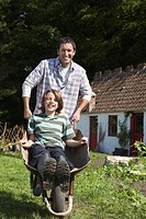 Father pushing son 7_9 in wheelbarrow outside cottage portrait