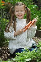 Girl 5_6 holding carrots in garden portrait