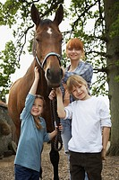 Mother and children 5_6 7_9 with horse outdoors portrait