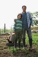 Father standing with arm round son 7-9 in sty with pig portrait (thumbnail)