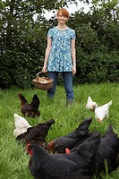 Woman holding egg basket by hens in garden portrait