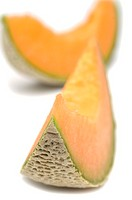 Slices of cantaloupe melon on white background