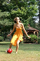 Girl in her 20's in a summer dress having fun playing soccer barefooted in a park