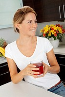 Woman In Kitchen Drinking Cranberry Juice