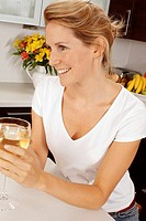 Woman In Kitchen Drinking Glass Of White Wine